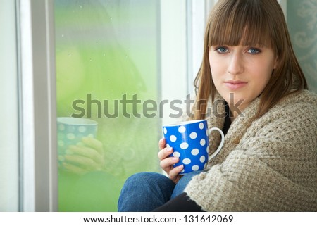 Close up portrait of a young woman relaxing by window with cup of tea - stock photo