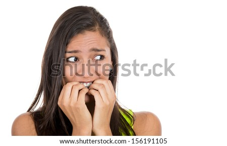 Close-up portrait of a young woman scared ,afraid and anxious biting her finger nails, looking away on to the side, with wide opened eyes isolated on a white background. Human emotions - stock photo