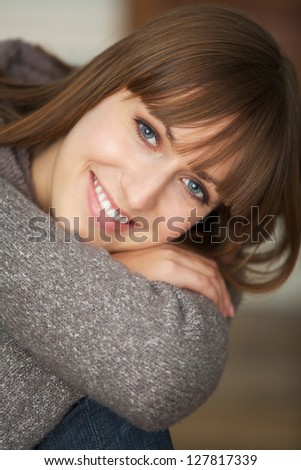 Close up portrait of a young woman smiling indoors - stock photo
