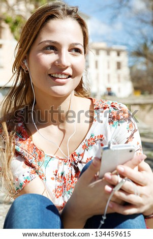 Close up portrait of a young woman using a smartphone to listen to music with her head phones, sitting outdoors in the city on a sunny day. - stock photo