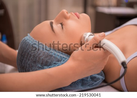 Close-up portrait of a young woman with a towel on her head lying on a table with closed eyes getting a laser skin treatment in healthy beauty spa salon - stock photo