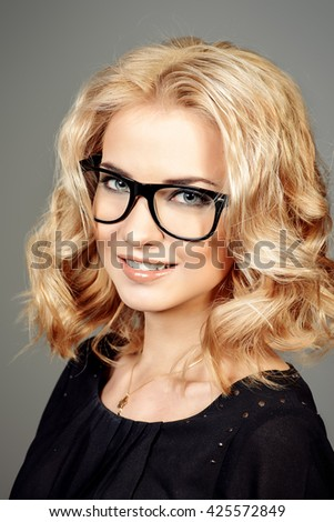 Close-up portrait of a young woman with beautiful blonde hair wearing glasses. Optics. Eyewear style. - stock photo