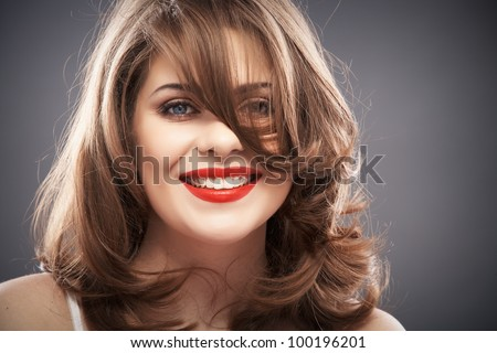 Close up portrait of a young woman with long curly hair on gray background isolated. Smiling happy girl