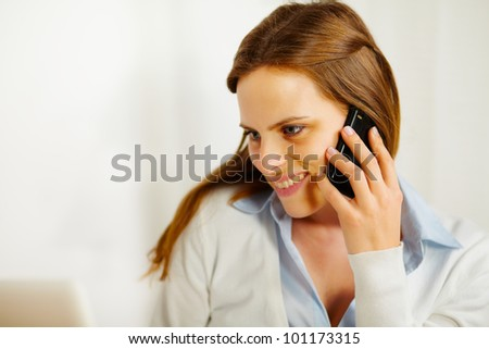 Close up portrait of a young woman working on laptop while talking on the phone - stock photo