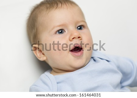 Close up portrait of adorable happy baby boy with blue eyes and mouth open. - stock photo