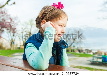 Close up portrait of adorable little girl resting in a park - stock photo