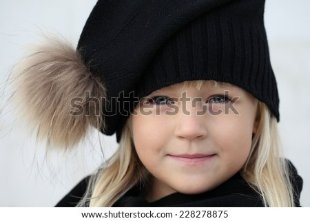 Close-up portrait of adorable smiling child girl wearing knitted hat