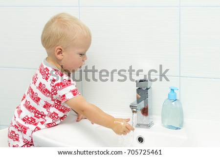 Close-up portrait of adorable white Caucasian boy toddler one year old washing hands in bathroom and looking surprised excited, playing with water.