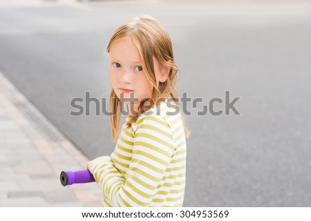Close up portrait of adorable young 8 years old girl leaning on his scooter - stock photo