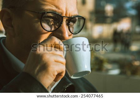 Close up portrait of adult male drinking coffee outdoors at daytime - stock photo