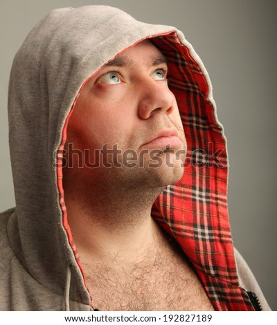 Close-up Portrait of adult thinking  man in the hood looking sideways and upwards . Gray background