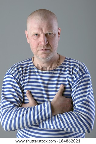 close-up portrait of adult white bald men in striped vest  with a serious look studio