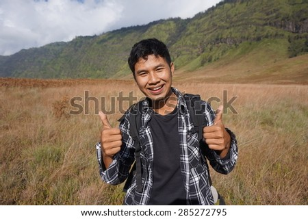 Close up portrait of adventure man on the mountains with thumb - stock photo
