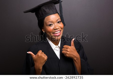 close up portrait of african female university graduate thumbs up - stock photo