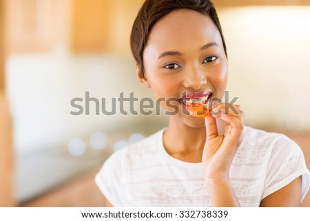 close up portrait of african girl eating a slice of tomato