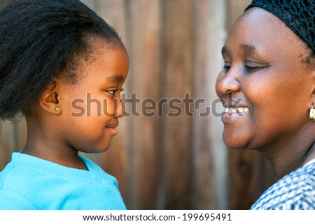 Close up portrait of African mother and daughter looking at each other. - stock photo