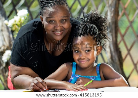 Close up portrait of african mother and little daughter with braided hairstyle in garden.Girl drawing on paper with color pencils outdoors. - stock photo