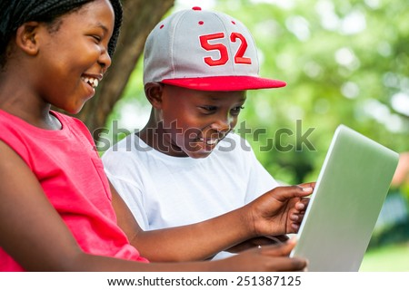 Close up portrait of African youngsters enjoying time with laptop in park. - stock photo
