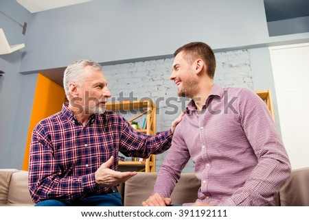 Close up portrait of aged father having talk with his adult son - stock photo