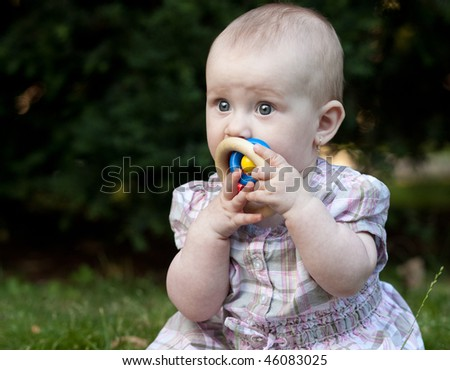 close-up portrait of an adorable toddler sitting on a lawn in a park - stock photo