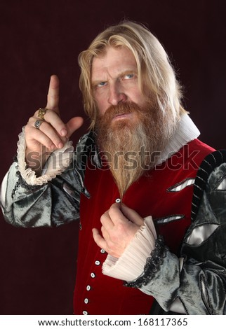 close-up portrait of an adult male with a beard and mustache in medieval costume makes a gesture index finger up. studio on a burgundy background - stock photo