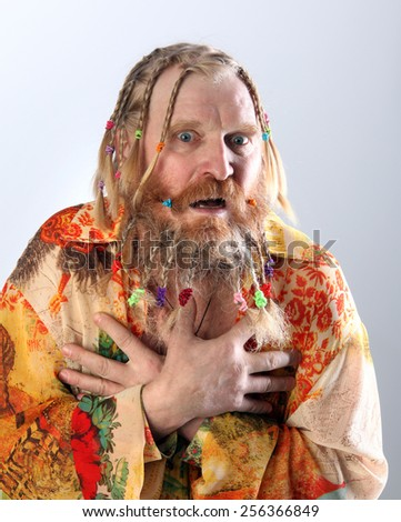 close-up portrait of an adult male with long beard, mustache and hair braided in pigtails gesturing studio on light background - stock photo