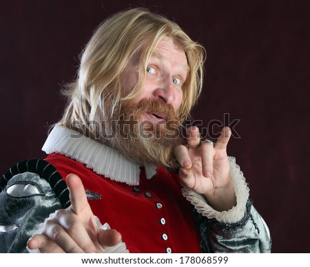close-up portrait of an adult male with long blond hair beard and mustache in medieval costume studio on a burgundy background - stock photo