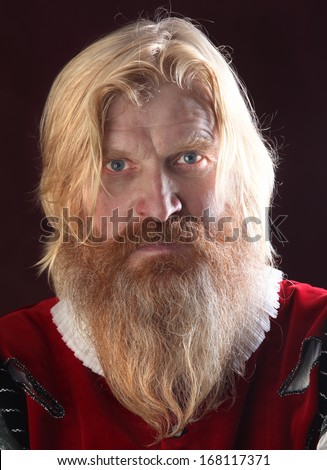 close-up portrait of an adult male with long blonde hair with a mustache and beard in medieval costume studio on a burgundy background - stock photo