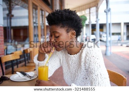 Close up portrait of an african american woman drinking orange juice at outdoor cafe