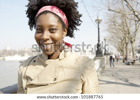 Close up portrait of an african american woman smiling happily at camera standing by the river Thames in London. - stock photo