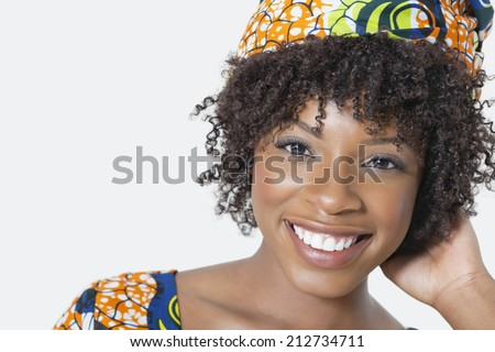 Close-up portrait of an African American woman smiling over gray background - stock photo