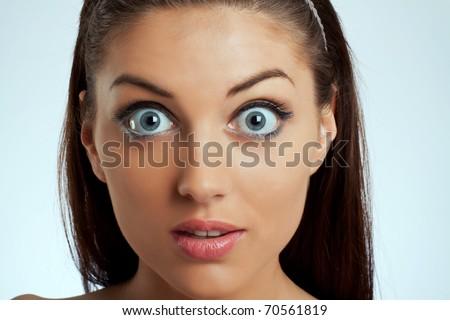 Close-up portrait of an amazed female on white background - stock photo
