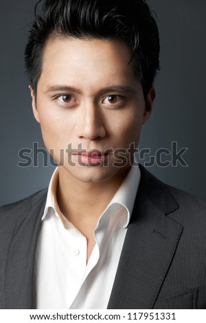 Close up portrait of an Asian businessman in studio with gray background - stock photo