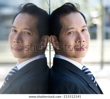 Close up portrait of an asian businessman with mirror reflection - stock photo