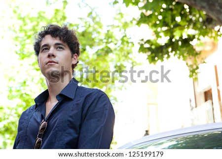 Close up portrait of an aspirational businessman wearing an elegant shirt and leaning on a car, looking away with trees in the background. - stock photo