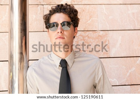 Close up portrait of an aspirational businessman wearing shades and leaning on a modern building in the city. - stock photo