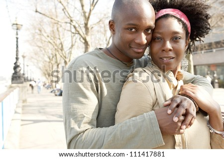 Close up portrait of an attractive african american couple visiting London and hugging while on vacation. - stock photo