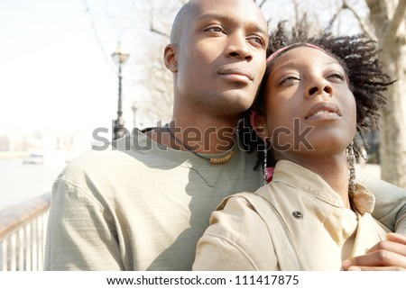 Close up portrait of an attractive african american couple visiting London city and hugging while on vacation. - stock photo