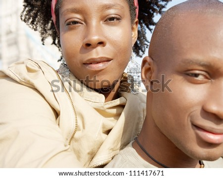 Close up portrait of an attractive african american couple with their heads together standing by the Tower of London while on vacation. - stock photo