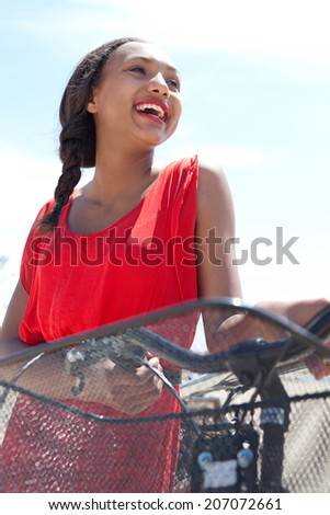 Close up portrait of an attractive african american teenager girl holding her bicycle, joyfully laughing against the blue sky during a sunny day on holiday. Active and healthy lifestyle, outdoors. - stock photo