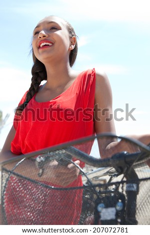 Close up portrait of an attractive african american teenager girl holding her bicycle, joyfully smiling against the blue sky during a sunny day on holiday. Active and healthy lifestyle, outdoors. - stock photo