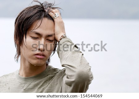 Close up portrait of an attractive and depressed asian japanese young man by a lake being thoughtful and relaxing during a rainy winter day with wet hair and skin, outdoors. - stock photo