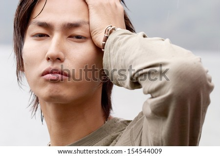 Close up portrait of an attractive asian japanese young man by a lake being thoughtful and relaxing during a rainy winter day with wet skin. In tune with nature, outdoors.