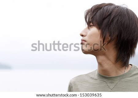 Close up portrait of an attractive asian japanese young man standing by a lake being thoughtful and relaxing during a rainy winter day. In tune with nature, outdoors. - stock photo