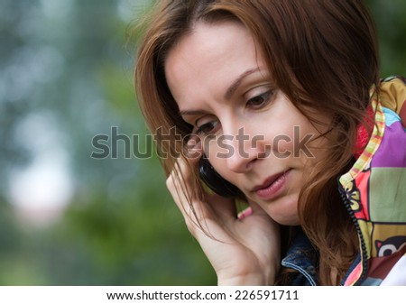 Close up portrait of an attractive beautiful pretty cute young caucasian woman (lady, girl, female, person, model) speaking by mobile phone - concept of communication. - stock photo