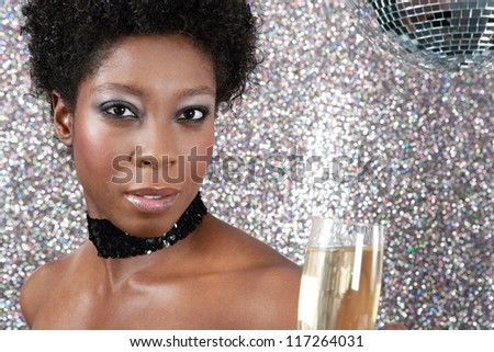 Close up portrait of an attractive black woman holding an champagne glass against a silver glitter background and next to a mirror ball. - stock photo