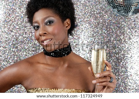 Close up portrait of an attractive black woman holding an champagne glass against a silver glitter background and next to a mirror ball.