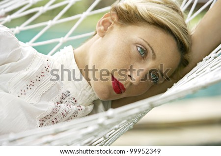 Close up portrait of an attractive blonde woman laying down on a hammock in a garden. - stock photo