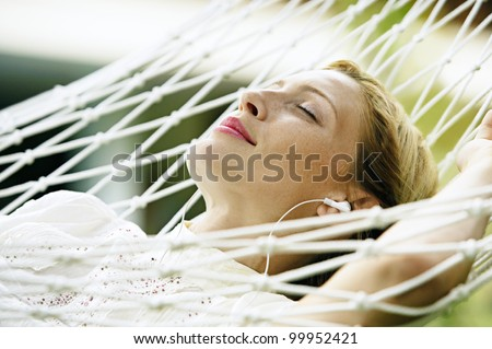 Close up portrait of an attractive blonde woman laying down on a hammock listening to music, with her eyes closed and smiling. - stock photo