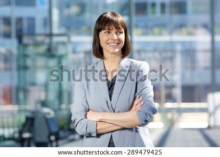 Close up portrait of an attractive business woman smiling with arms crossed in the city - stock photo